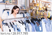 Купить «Woman customer choosing blue blouse in the fashion store», фото № 28917785, снято 15 марта 2018 г. (c) Яков Филимонов / Фотобанк Лори