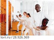 Купить «Active african american male fencer in uniform standing with mask and foil at fencing room», фото № 28926369, снято 11 июля 2018 г. (c) Яков Филимонов / Фотобанк Лори
