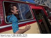 Купить «Молодой человек в одежде 1950-х, 1960-х годов едет в старом автобусе по Тверской улице города Москвы, Россия», фото № 28935221, снято 10 августа 2018 г. (c) Николай Винокуров / Фотобанк Лори