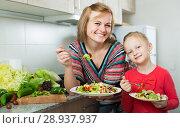 Купить «Happy mother and daughter eating vegetable salad», фото № 28937937, снято 14 августа 2018 г. (c) Яков Филимонов / Фотобанк Лори