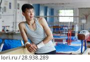 Купить «Positive young man asian acrobat posing at modern sport gym», фото № 28938289, снято 18 июля 2018 г. (c) Яков Филимонов / Фотобанк Лори