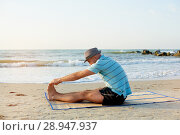 Купить «Fit man stretching outside morning warm-up, view at sea. Fitness and sport concept», фото № 28947937, снято 2 августа 2018 г. (c) Happy Letters / Фотобанк Лори