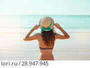 Купить «Summer lifestyle portrait of pretty young suntanned woman in a hat. Enjoying life and sitting on the beach, time to travel. Looking at the sea», фото № 28947945, снято 4 августа 2018 г. (c) Happy Letters / Фотобанк Лори