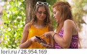Купить «teenage girls with smartphones in summer park», видеоролик № 28954169, снято 1 августа 2018 г. (c) Syda Productions / Фотобанк Лори
