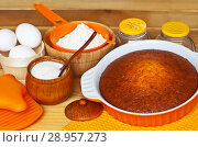 Купить «Freshly baked homemade cake in orange baking dish and ingredients for dough preparation: chicken eggs, sugar, flour and spices on a wooden background. Culinary Still Life. Close-up view», фото № 28957273, снято 16 июля 2018 г. (c) Виктория Катьянова / Фотобанк Лори