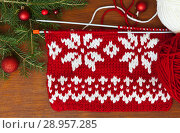 Купить «Red and white hand knitting on knit-needles at a wooden background near the Christmas tree», фото № 28957285, снято 19 июля 2018 г. (c) Виктория Катьянова / Фотобанк Лори