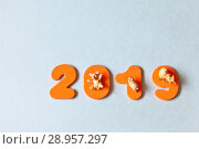 Купить «Three merry little pigs - a symbol of the New Year 2019 on the eastern calendar on bright numbers. A lot of free space for greetings and text on a light background similar to snow», фото № 28957297, снято 25 июля 2018 г. (c) Виктория Катьянова / Фотобанк Лори