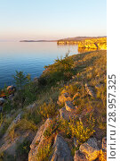 Купить «Lake Baikal. Summer warm evening on the Olkhon Island. The grass and wild flowers on the slopes of the coastal rocks. Beautiful summer calm landscape», фото № 28957325, снято 8 августа 2018 г. (c) Виктория Катьянова / Фотобанк Лори