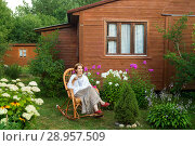 Купить «A calm woman with a Cup of tea is sitting in a chair at the country house», фото № 28957509, снято 4 августа 2018 г. (c) Юлия Кузнецова / Фотобанк Лори
