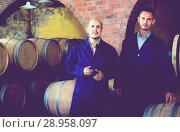 Купить «two cheerful men in uniforms standing in cellar with wine woods», фото № 28958097, снято 15 октября 2018 г. (c) Яков Филимонов / Фотобанк Лори