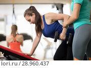 Купить «Fitness trainer helping young girl doing exercises in gym», фото № 28960437, снято 26 июня 2019 г. (c) Оксана Кузьмина / Фотобанк Лори
