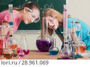 Купить «two girls doing chemical experiments», фото № 28961069, снято 17 февраля 2018 г. (c) Майя Крученкова / Фотобанк Лори
