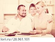 Купить «Happy parents with son looking at documents», фото № 28961101, снято 12 ноября 2017 г. (c) Яков Филимонов / Фотобанк Лори