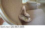Купить «Bridal wedding beautiful shoes hon a white armchair luxury heeled closeup», видеоролик № 28967005, снято 9 августа 2018 г. (c) Aleksejs Bergmanis / Фотобанк Лори