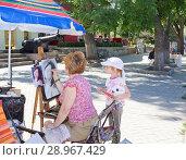 Купить «A little girl watching the work of a street artist», фото № 28967429, снято 11 июня 2014 г. (c) Олег Хархан / Фотобанк Лори