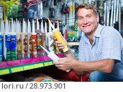 Купить «Man customer picking sealing component», фото № 28973901, снято 8 июля 2020 г. (c) Яков Филимонов / Фотобанк Лори