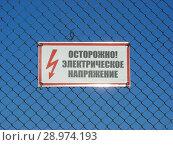 """Купить «Предупреждающий знак электробезопасности """"Осторожно! Электрическое напряжение""""», эксклюзивное фото № 28974193, снято 6 мая 2015 г. (c) lana1501 / Фотобанк Лори"""