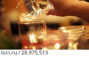 Купить «The bartender pours a drink from one glass to another glass», видеоролик № 28975513, снято 4 апреля 2020 г. (c) Константин Шишкин / Фотобанк Лори