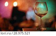 Купить «Empty glass of wine stands on the bar, in the background musicians and glare from the lights», видеоролик № 28975521, снято 4 апреля 2020 г. (c) Константин Шишкин / Фотобанк Лори