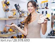 Купить «Young woman standing with chosen shoe», фото № 28978693, снято 20 сентября 2018 г. (c) Яков Филимонов / Фотобанк Лори