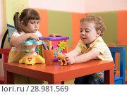 Купить «Children girl and boy play in kids daycare center», фото № 28981569, снято 21 сентября 2018 г. (c) Оксана Кузьмина / Фотобанк Лори
