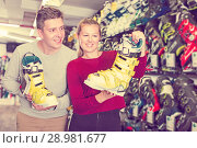 Купить «Woman with man are choosing boots for skiing», фото № 28981677, снято 31 июля 2017 г. (c) Яков Филимонов / Фотобанк Лори