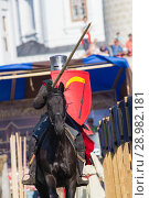 Купить «Bulgar, Russian Federation - August 2018, - a man dressed as a knight with a red coat of arms participates in the festival of the middle ages», фото № 28982181, снято 11 августа 2018 г. (c) Константин Шишкин / Фотобанк Лори