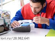 Купить «The man repairman repairing iron at service center», фото № 28982641, снято 11 июля 2017 г. (c) Elnur / Фотобанк Лори