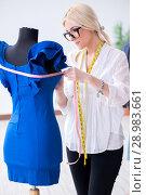 Купить «The woman tailor working on new dress designs», фото № 28983661, снято 13 апреля 2018 г. (c) Elnur / Фотобанк Лори