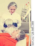 Купить «Woman client checking result of beauty procedures», фото № 28985349, снято 21 февраля 2019 г. (c) Яков Филимонов / Фотобанк Лори