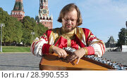 Купить «Folk minstrel in traditional Russian clothes plays an old Russian musical instrument gusli on the background of the Kremlin and St. Basil's Cathedral on red Square. Moscow, Russia», видеоролик № 28990553, снято 26 августа 2018 г. (c) Алексей Кузнецов / Фотобанк Лори