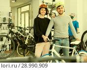 Купить «Active couple in helmet standing near bicycle», фото № 28990909, снято 8 января 2018 г. (c) Яков Филимонов / Фотобанк Лори