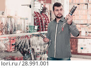 Man choosing new glue gun. Стоковое фото, фотограф Яков Филимонов / Фотобанк Лори