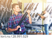 Купить «Young cheerful male is choosing air-powered gun», фото № 28991029, снято 4 июля 2017 г. (c) Яков Филимонов / Фотобанк Лори