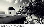 Church dome with wind playing with flower shrub on a terrace of traditional cafeteria in typical greek village of Oia, Santorini island, Greece. Стоковое видео, видеограф Matej Kastelic / Фотобанк Лори