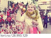 Купить «Happy mature woman in tinsel with Christmas toys at fair», фото № 28993129, снято 21 декабря 2017 г. (c) Яков Филимонов / Фотобанк Лори