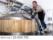 Купить «Brewer is controls the brewing process near reservoir with beer», фото № 29004785, снято 18 сентября 2017 г. (c) Яков Филимонов / Фотобанк Лори