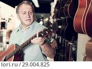 Купить «Man customer choosing new wooden acoustic guitar», фото № 29004825, снято 18 сентября 2017 г. (c) Яков Филимонов / Фотобанк Лори