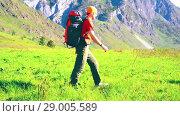 Купить «Hiking man walking on green mountain meadow with backpack. Summer sport and recreation concept.», видеоролик № 29005589, снято 17 апреля 2018 г. (c) Александр Маркин / Фотобанк Лори