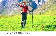 Купить «Hiking man walking on green mountain meadow with backpack. Summer sport and recreation concept.», видеоролик № 29005593, снято 23 апреля 2018 г. (c) Александр Маркин / Фотобанк Лори