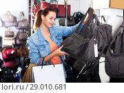 Купить «Girl buying handbag in fashion shop», фото № 29010681, снято 15 сентября 2016 г. (c) Яков Филимонов / Фотобанк Лори
