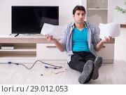 Купить «Man trying to fix broken tv», фото № 29012053, снято 9 марта 2018 г. (c) Elnur / Фотобанк Лори