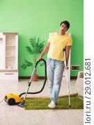 Купить «Injured man on crutches vacuum cleaning house», фото № 29012681, снято 30 мая 2018 г. (c) Elnur / Фотобанк Лори