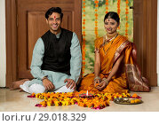 Happy maharashtrian couple in traditional dress sitting near entrance with flower decorations pooja plate and diya on the floor. Стоковое фото, фотограф IndiaPicture / easy Fotostock / Фотобанк Лори