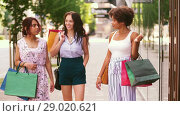 Купить «happy women with shopping bags walking in city», видеоролик № 29020621, снято 15 августа 2018 г. (c) Syda Productions / Фотобанк Лори