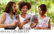 Купить «women with city guide and drinks on street», видеоролик № 29020677, снято 15 августа 2018 г. (c) Syda Productions / Фотобанк Лори