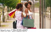 Купить «women with shopping bags looking at shop window», видеоролик № 29020697, снято 15 августа 2018 г. (c) Syda Productions / Фотобанк Лори