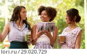 Купить «women with city guide and drinks on street», видеоролик № 29020729, снято 15 августа 2018 г. (c) Syda Productions / Фотобанк Лори