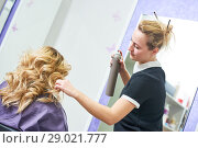 Купить «hairdo in beauty salon. hairdresser fixing hair with hairspray», фото № 29021777, снято 28 марта 2017 г. (c) Дмитрий Калиновский / Фотобанк Лори