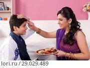 Купить «Sister applying tilak to her brother at Raksha Bandhan», фото № 29029489, снято 8 октября 2013 г. (c) easy Fotostock / Фотобанк Лори
